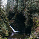 The view of Upper Goldstream Falls from the small rocky beach at the bottom of the stairs.